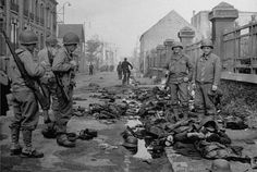 Army soldiers look over the corpses of German victims of an Allied mortar attack during the Battle of Cherbourg, part of the larger Battle of Normandy. In the distance, French civilians wander.