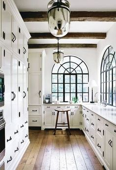 Elegant white kitchen space with arched windows | Jacquelyn Clark