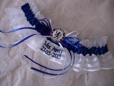 Chelsea Football Club wedding garter in white satin-striped organza and navy blue satin. The badge charm, and embroidery personalization, add additional customization.