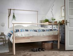 A bed in untreated solid wood with a headboard with a rounded rail for hanging clothes or draping a fabric.