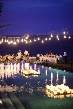Tea lights floating in a pool I via Colin Cowie