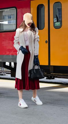 Fashion blogger Veronika Lipar of Brunette from Wall Street wearing brown baseball hat Harris Wharf pink coat with pink blouse and red pleated midi skirt with Veja sneakers on the train station Movie Night Outfits, Casual Date Night Outfit, Winter Date Outfits, Cute Date Outfits, Casual Date Nights, Stylish Winter Outfits, Veja Sneakers, Jeans And Sneakers, Dress With Sneakers