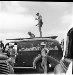 There are so many amazing things about this photo: that pose, for one (leg out, stomach in, shoulders back--take notes, people), the car paneling, the dog and guy just chillin' on the vehicles roof... #JustAnotherAfternoonAtTheBeach