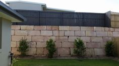 Sandstone retaining wall with painted fence. Love how the green contrasts with the grey