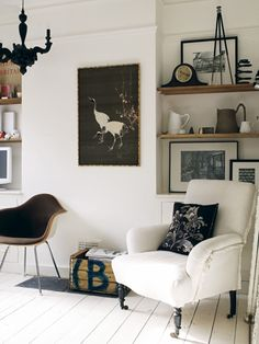 I love a chair on an angle // also I love the wooden floating shelves against the stark white walls.