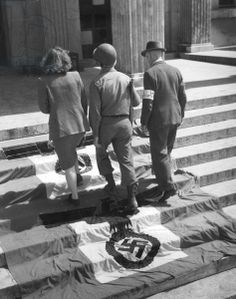 An American soldier with an employee of the military administration and a civilian policeman, in Koenigsplatz, Munich, 1945 (b/w photo)