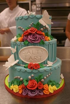 Blue wedding cake with butterflies and rainbow flowers