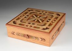 An inlaid marquetry box, comprised of a square shape and hinged lid, circa 1979s.