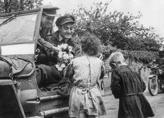 Two Royal Air Force officers are presented with flowers by French children in France on June 10, 1944.