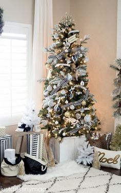 Black-and-white striped ribbon wraps around a Christmas tree that's adorned with flocked branches and faux marble ornaments.