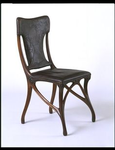 Chair | Made in Paris ca. 1900 | Designer: Eugène Gaillard (1862-1933)  |  Maker: Siegfried Bing (1838-1905) | Materials: carved walnut, upholstered in embossed and stained leather | Gaillard believed that ornament should be inspired by nature, but that designers should not simply copy natural forms. The carved walnut frame appears to 'grow' organically, like the branches of a tree | VA Museum, London