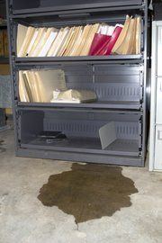 A puddle next to a cabinet in a dingy, forgotten filing room marks the presence of water. Records Management, Filing, Cabinet, Water, Room, Collection, Clothes Stand, Gripe Water, Bedroom