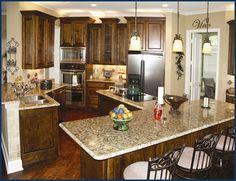 Dark kitchen cabinets, wood floors, granite counter tops, and pendant lighting. Almost exact to my new kitchen!