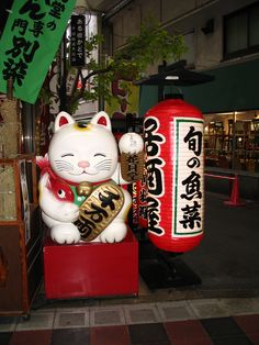Maneki neko in Osaka outside  a lantern shop.  A common Japanese talisman which is believed to bring good luck to the owner. Traditionally, a calico Japanese Bobtail beckons with an upright paw. Often displayed at the entrance of shops, restaurants, pachinko parlors, and other businesses.