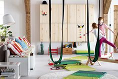 Two kids on IKEA balance beams in a room set up with gymnastic toys.