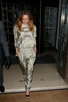 Stella McCartney in a shimmering metallic gold top and trousers with black pumps.