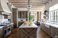 Antique Tunisian tile from Exquisite Surfaces makes a lively backsplash in Gisele Bündchen and Tom Brady's Los Angeles kitchen, which is appointed with Formations pendant lights, marble countertops from Compas Architectural Stone, custom-made alder cabinetry, an oak island, and a Wolf range.Pin it.