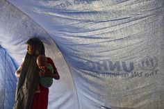 A Somali refugee stands inside a tent with her baby in Dollo Ado, Ethiopia. UN Photo/Eskinder Debebe. Un Refugee, Refugee Crisis, Refugee Camps, Somali Refugees, Across The Border, United Nations, Ethiopia, Priest, Human Rights