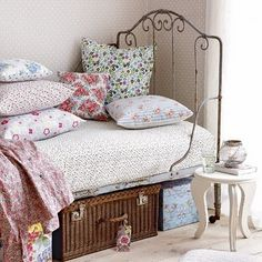 Floral pillows, pink and blue girl's bedroom.  Pretty baskets and boxes under the bed for storage.