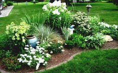 parterre de fleurs blanches, plantes vertes et jardine en gazon