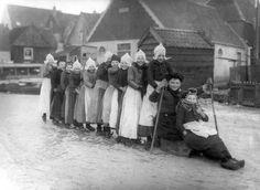 Kinderen in klederdracht vormen een rij op schaatsen achter een prikslee/prikslede op het ijs te Volendam, 16 januari 1914.