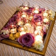 Framed Votive and Flower Centerpiece. Take a picture frame, spray paint it, add filer and lots of little votive candles. Could also add a single small vase in the center with a few flowers. Possibly do this for some tables and the bowl with the floating candles for the others?