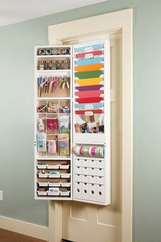 """The Over-The-Door Craft Armoire from Jinger Adams has a cork front, closing magnetic door and can also be mounted to a wall. Other features include: Four drawers and four craft trays Six large and three small clear pockets Five paintbrush and/or pen holders Eleven 12"""" x 12"""" paper trays and one ribbon rod Six scissor hooks Two storage shelves"""
