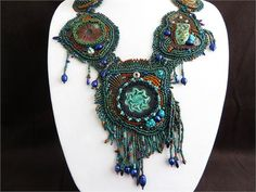 This unique one of a kind statement necklace is created with bead embroidery and freeform peyote seed bead stitch.The necklace is not from a pattern but evolved from my imagination as it was being beaded. The result is quite dramatic, bold and chunky. The five pendants are created with handmade Raku kiln fired clay cabochons. The pendants are backed with ultra suede. They are stitched together with freeform peyote stitch. The necklace straps have also been bead woven with freeform peyote…
