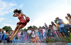 UKRAINE, Kiev: A girl jumps over a campfire while celebrating Ivan Kupala Night, a traditional Slavic holiday not far from Kiev on July 6, 2013. During the celebration, originating in pagan times, people plait wreaths, jump over fires, and swim naked. AFP PHOTO/ SERGEI SUPINSKY