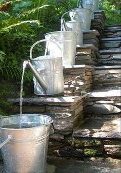 watering can waterfall fountain just need an outdoor pump some tubing and watering cans this is the basic idea of filtering water through drums to save