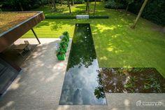 Aangelegde tuinen door tuinonderneming Monbaliu - Strakke tuin in bosrijk gebied, met ruime oprit, parking en een lange zwemvijver die dwars door het gras