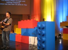 Giant LEGO's - They created these boxed from colorful Coroplast. They made the connecting tops out of Christmas cookie tines they bought at a dollar store. Legos, Maker Fun Factory Vbs, Kids Stage, Lego Wall, Vbs Themes, Church Stage Design, Lego Room, Lego Birthday, Vacation Bible School