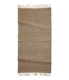 Rectangular, striped rug in jute and cotton jersey with fringe at ends.