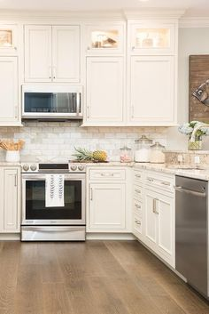 White u-shaped kitchen boasts square cabinets fitted with custom lighting and stacked above white cabinets adorning polished nickel pulls and flanking a wall mounted stainless steel microwave fixed against marble subway backsplash tiles above a stainless steel range.