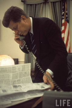 JFK multi-tasking - reading the paper and talking on the phone in the Oval…