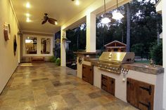 37x10.5 slate tiled back patio with summer kitchen.  Includes grill, sink, and refrigerator in cabinet.