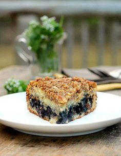 Blueberry Walnut Coffee Cake...Extremely moist and tender with a blueberry nut filling in the center and a delicious crumb topping to finish it off. Grab yourself a cup of coffee, this cake is a delicious treat for blueberry lovers!