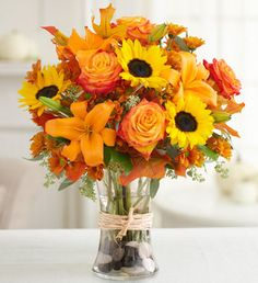"""Beautiful bouquet of roses, sunflowers, lilies, daisy poms, seeded eucalyptus, and salal, accented with preserved Fall leaves."""