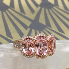 To call this 3-stone padparadscha sapphire ring rare is an understatement. It is nearly impossible to color match padparadscha sapphires as this color designation ranges greatly, from pinkish-orange to orange-pink. Finding fine quality padparadscha's over 2 carats is very uncommon, but here in this 18K rose gold ring are over 7 carats of matching, no heat oval padparadscha sapphires. #OnlyOmi #ohmyomi #omiprive