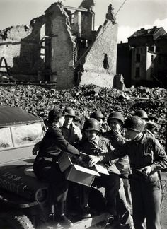 American soldiers receive doughnuts from a Red Cross worker in the streets of Aachen, Germany in October,1944