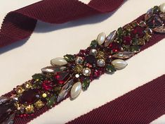 Garnet, Burgundy, Rose Gold, Olive, and Ivory Pearl Holiday Crystal Embellished Multi Colored Bridal Grosgrain Ribbon Sash Belt. Deep saturated crystals perfectly suited for a winter holiday wedding. This stunning bridal bridesmaids sash features an array of colorful crystals in a