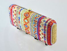 This exquisite hand crafted Swarovski Crystal Indian inspired Bridal clutch has been adorned in a multitude of Red, Green, gold, sapphire Aquamarine crystals that all complement each other. There are over 5000 crystals that have been hand applied to this clutch in an aztec style replicated pattern. The pictures do not do this item justice!  Details & Fit  • Patterned Rectangular Clutch Bag • Metal hard case • Crystal embellished body in Multi Colour Crystals • Optional metal chain strap ...
