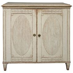 Period Gustavian Sideboard, Sweden, circa 1800, with two doors under a shaped top and dentil molding. Each of the doors has a bellflower frieze at top and bottom and a large reeded oval in the center.