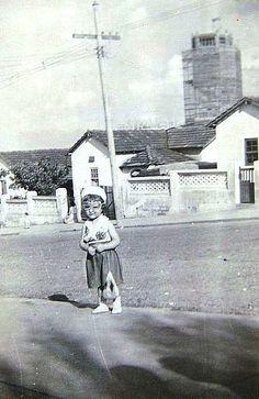 Época de carnaval. Na Avenida Norberto Mayer, Vila Santa Isabel, Avenida Norberto Mayer, Vila Santa Isabel (anos 50). A pequenina Cássia, em frente de casa. Ao fundo, a torre do Santuário Santa Isabel Rainha, em construção. Colaboração: Claudete Zuchieri.