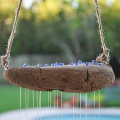 A way to attach your strings of shells - through drilled holes in the driftwood, and secured with beads on the top of driftwood.