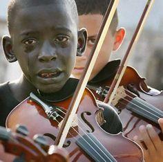 Diego Frazão Torquato, en pleurs, jouant du violon aux funérailles de son professeur qui l'a aidé à sortir de la misère.