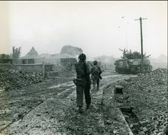 """The caption on this photograph reads """"Entering Naha-The outskirts of Naha, capital city of Okinawa bears the scars of aerial and artillery barrages as Sixth Division tanks and riflemen forge into the town."""" Entering Naha, Okinawa, May 1945"""