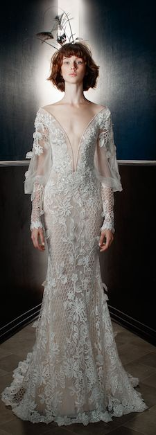 The Lia. A sheer 3D lace gown with open work fish net elements, a low plunging V neckline, and sheer Victorian sleeves with lace cuffs. The gown has a light powder pink background and the lace is embroidered with silver thread. The neckline is embroidered with an antique Victorian embroidery. The back has a very low V and is laced all the way down. #wedding #dress #couture #bride