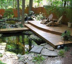carpes koï dans le bassin à poisson à côté de la terrasse de jardin en bois