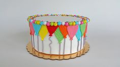 Fondant birthday cake. Rainbow balloon design, malt candies & sprinkles. A cheery and festive birthday cake.